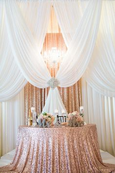 pipe and drape backdrop to a half moon sweetheart table in sequin rose gold
