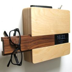 "The Butler wall-mounted wood dock by Curtis Micklish is designed to fit your wallet and keys in the top sleeve, your iphone on the side slot with a concealed space for your charging cord, and glasses/hat/scarf or whatever other go-to item on the slide out walnut piece. Dimension: 10"" wide x 9"" tall x 2 1/4"" thick."