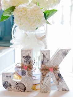 The couple's initials wrapped in illustrated book pages and tied with twine / bows as wedding centerpieces.