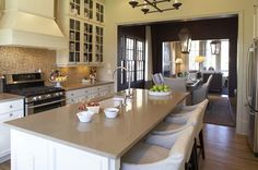 Westbrook Interiors - kitchens - ivory, brown, gold, mosaic, tiles, backsplash, ivory, glass-front, cabinets, kitchen, island, slip-covered, French curve range hood, stools, iron, chandelier, gray, corian, countertops,