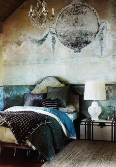 Walls that look as if they've been around for years have vintage charm to them.  Recreate this room with a distressed stone slab wallpaper and contrast it with luxurious fabrics and patterns like silk, velvet and paisley.  Here the upholstered headboard and pillows create softness that balance out the shabby-chic walls.