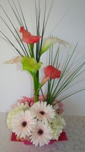 Calla Lilies, Hydrangeas & Daisies  This silk floral arrangement has a base of white and pink hydrangeas with white/lt.pink gerbera daisies and deep pink gerbera daisies. Rising up from the center, grouped together by colored deco wire, are white, coral, and light green calla lilies.