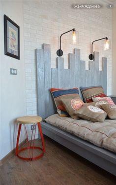 Спальня. Изголовье кровати из крашеных досок, подушки из рогожки, металлические светильники и красная металлическая табуретка (столик)