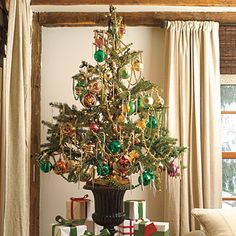 Colorful Tabletop Display:     If you're tight on space, try a tabletop tree planted in a sculptural garden urn. Dripping with antique glass ornaments and beaded garland, it's a festive way to display your treasures.
