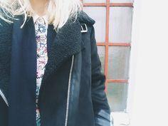 Bunte Bluse und schwarze Lederjacke.