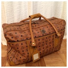 """✨CLEAR OUT✨MCM Signature XL Travel Duffle Bag ✨CLOSET CLEAR OUT✨ Placed in local consignment shop as of 12/03.   **VINTAGE** Authentic MCM XL travel duffle bag. Acquired this piece from my family storage but it was purchased at Saks. I'm not too familiar with the brand but the craftsmanship has stood the test of time! Leather could use reconditioning but otherwise no scratches/blemishes noted. Zippers are in excellent condition. Name tag attached. No shoulder strap. Approx 25""""L 15""""H 14""""W MCM…"""