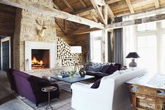 In the great room of her family's Idaho retreat, Mary Lynn Turner of M. Elle Design flanked a custom-made sofa and a stone-and-iron cocktail table from Lucca & Co. with a pair of George Smith sofas. The curtains are of a Holland & Sherry wool, the overhead beams are reclaimed white oak, and the oak floorboards were treated to appear aged.   - ELLEDecor.com