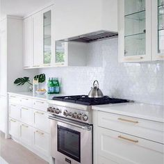 Beautiful white kitchen is equipped with a Thermador stove positioend between white shaker drawers accented with brass pulls and a white quartz countertop fixed against white geometric backsplash tiles. Copper Backsplash, Beadboard Backsplash, Herringbone Backsplash, Hexagon Backsplash, Mirror Backsplash, Glass Kitchen, Kitchen Backsplash, Countertop
