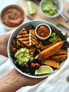 Taça de grelhados com batata-doce e tofu grelhados, salada de feijão preto e pimento, molho de tomate e pimento vermelho grelhados, e pasta de abacate (guacamole)