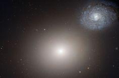 Messier 60, una galacia elíptica gigante de 120.000 años luz de diámetro y una galaxia más pequeña, la galaxia Espiral.