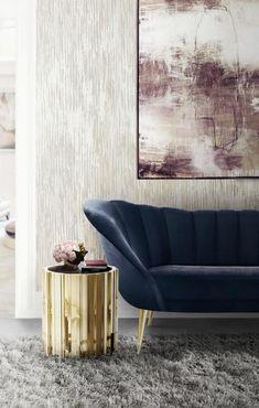 deco salon avec canapé en bleu pétrole, petite table ronde et basse dorée avec plan en noir, tapis effet fourrure en gris clair, murs en gris et noir