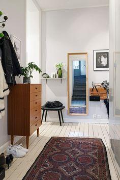 By optycznie poprawić proporcje tego wąskiego przedpokoju, zaprojektowano w nim szafę z błyszczącymi białymi frontami, która wtapia się w tło ściany. A naprzeciwko schodów zawieszono lustro, dzięki któremu wnętrze zyskało dodatkową perspektywę. Komoda w stylu vintage i etniczny chodnik na podłodze stworzyły eklektyczny wystrój.