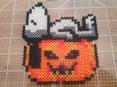 Halloween perler beads.  Snoopy sleeping on a Pumpkin.