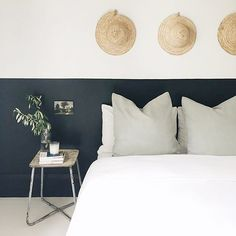 bedroom with black and white walls via sfgirlbybay | love the straw hats hanging above the bed | pale green/mint cushions off sets the crisp white bedlinen