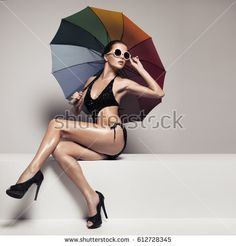 Beautiful woman in stylish black swimwear and sunglasses holding colorful umbrella. Perfect slim tanned body.