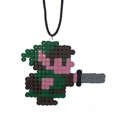 Zelda Necklace in the shape of Link from the famous Legend of Zelda video game series. Made from pink, green, brown, black and grey hama beads this Zelda Necklace is a fun gift for any fan or geek who likes Gaming Merchandise. Including a 30″ black cord you can shorten, this Zelda Necklace can be cut to your desired length or can be removed and placed on a silver necklace (Not supplied).