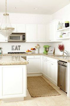White cabinets and wall, multicolored back splash, slightly darker floor