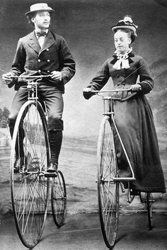 bicycling with bustle dress... (Though I think it's without a bustle, just a little more skirt in back... doesn't look like riding habit... those often had trousers under... I think the pedal system is fascinating. What balance!)