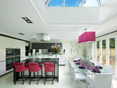 This airy kitchen feels open and inviting with its French doors, skylights and crisp, white-on-white color scheme. To add a modern edge, the designer included sharp black and fuchsia accents in the barstools, place settings and geometric light fixture. Using deeper contrasts in the kitchen helps create a barrier between the two areas, creating a softer, more intimate space in the dining room.