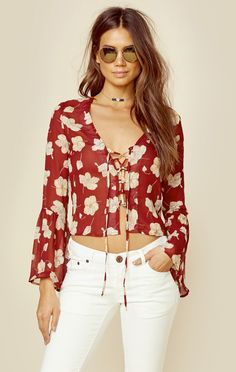 This pretty blouse by Flynn Skye is the Boston Top. Featuring a floral print throughout, long bell sleeves, sheer fabrication, and lace up detailing in the front.   Made in USADry Clean OnlyRayon Blen