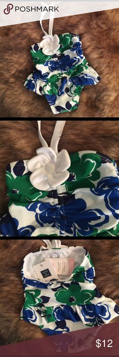 JANIE and JACK Flowered Baby Swimsuit This is too cute and made with UV Protection for that special baby girl. It is brand new with tags age and perfect green and blue fliers in white with hiking neck strap. It has a white flower on a he front and ruffle around hips. If you have a baby 3-6 months in your life .. you need this! It is made of 81% Nylon and 19% Spandex. Fully lined and comfy and soft and stretchy for baby. Janie and Jack Swim One Piece