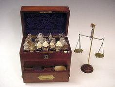 A Complete Apothecary Traveling Set, England, 1790 ca. Mahogany and brass box, with a lower drawer in the front. By opening the top, secured with singes on the back, the upper part reveals an internal cover in blue silk with a group of glass bottles ( some with labels) placed in separate compartments. Inside the drawer a little mortar and a scale.
