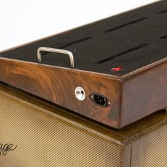 Dark hardwood walnut pedalboard with a fantastic fold off Zombie Tweed case.