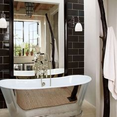 A Manhattan bath features sconces and a tub by Urban Archaeology, and a branch sculpture from Wyeth.