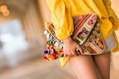 Invest in a statement cluch for a holiday ! We love this with pom-poms and coins and a great colorful print
