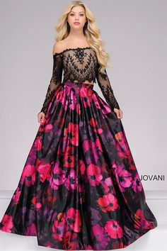 Gorgeous black and multi color floor length two piece prom ballgown features off the shoulder long sleeve lace crop top with nude underlay and a floral print pleated skirt.