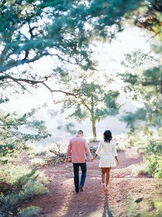 Couple walking hand in hand through nature. Sedona engagement shoot
