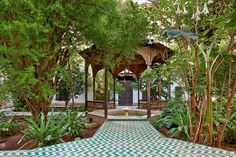 Green White Zigzag Tiled Path & Fountain in a riad garden at Dar Si Said. The kiosk is painted with flowers - Brugmansia arborea flowers in the beds. Moroccan Gardens.