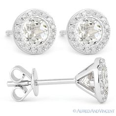 The featured earrings showcase round cut white topaz gems set flush in 14k white gold 3-prong settings topped with a diamond-encrusted halo then finished with push-backs for secure wear.