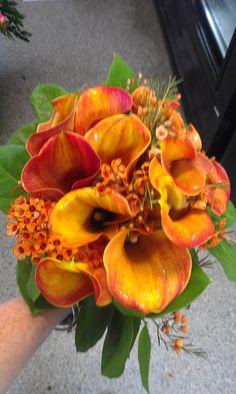 handheld bouquet of orange cala lilies