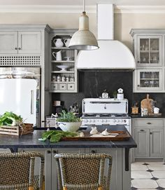 Offsetting the gleaming white appliances in this California home: an island with dark soapstone counters and backsplashes, as well as ash cabinetry painted a muted gray-green (Paris Gray by Annie Sloan Chalk Paint). The wicker stools are by Palecek. Kitchen Stools, New Kitchen, Kitchen Dining, Kitchen Decor, Bar Stools, Kitchen Ideas, Bistro Kitchen, Smart Kitchen, Room Kitchen