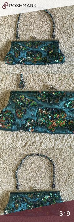 "Bisou Bisou sequenced satin green clutch butterfly Fun satin sequences small handbag in an emerald green color with beaded strap.  Handbag features top snap silver metal closure, satin lined inside with small pocket for credit cards, beautiful beaded strap that is 19"" in length with a 6.5"" strap drop. Dimensions include: 9"" length, 4"" height, 1"" width. Purse has a beautiful sequin and beaded pattern with butterfly and flowers. Purse is in excellent condition and was only used once. Bisou…"