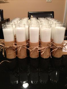 Dollar store candles, wrapped in burlap with a raffia bow.