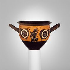 Terracotta mastoid (drinking cup with narrow base)  Period: Archaic Date: ca. 500 B.C. Culture: Greek, Attic Medium: Terracotta Dimensions: H. 3 1/4 in. (8.3 cm); diameter 4 1/8 in. (10.5 cm); width with handles 6 1/8 in. (15.6 cm) Classification: Vases Credit Line: Rogers Fund, 1941