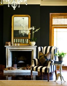 Fab black and white striped chair but also loving the large gold mirror and dark walls