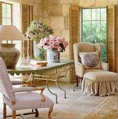 Walls, shutters and floors that have old world charm. Love the fabric on the chair and ottoman
