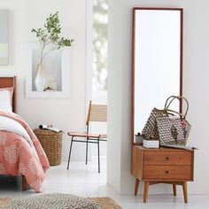 """Reflect on this. Full length and freestanding, the Mid-Century Storage Mirror yields a full-body view, with two drawers for hiding odds and ends. It's crafted from FSC®-certified wood, adding modern-day sustainability to its timeless style.  * 19""""w x 15.5""""d x 72.25""""h.  * FSC®-certified solid eucalyptus wood base, acacia wood veneer body; Acorn-stained finish.  * The FSC® promotes responsible forest management. Learn more.  * Mirrored glass.  * Made in Vietnam.  * Online/catalog only."""