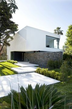 Contemporary home, white box over natural stone wall. large entrance steps