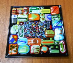 Fused Glass Patchwork Plate. I took a bunch of pendants and small fused glass pieces that I had made over the last couple of years but didn't love as jewelry pieces and put them together with multi colored frit in the middle. Came out pretty cool! - August 2013