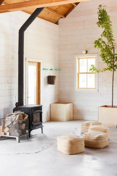Shed & Studio, Living Space Room Type, and Storage Space Room Type Shiplap pine walls, primed white, complement unfinished concrete floors and a wood stove by Jotul. Photo 3 of 7 in Get a Taste of Farm Life at a Cheery Guesthouse Outside Portland Shiplap Wood, White Shiplap Wall, White Wood Walls, Pine Walls, Pine Floors, Concrete Floors, Wood Stove Wall, White Cabin, Shed Interior