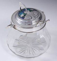 Archibald KNOX for Liberty & Co. Silver & Enamel Jam Pot with spoon. Powell glass jam pot with silver & enamel lid and spoon. Made in Birmingham 1906. Stamped William H. Haseler. (hva)