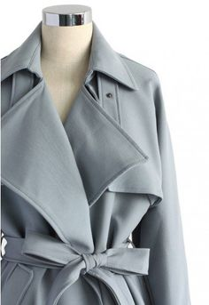 Cool grey! Step out in this subtly hued trench coat with its textured belt, storm flap, exaggerated lapels and cuffs decorating the sleeves and shoulders. The silhouette screams Sherlock Holmes without losing any of its model-esque charm. Wear this coat anywhere and stun inevitably.  - Waterfall drape in front - Open design - Belted waist and cuffs - Slant side pockets - Full lined - 100% Polyester - Machine washable  Size(cm) Length Bust Shoulder Sleeves XS        86     92 …