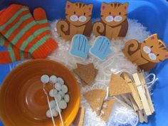 "Three Little Kittens Sensory Tub: ""Story cards are accented with 3 wood kittens, foam mitten stamps (perfect for creating patterns), yarn and clothespins to hang mittens, real pair of children's mittens, faux pieces of pie, snowballs and tongs!     Suggested filler ingredient : faux snow."""
