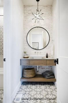 Round mirrors and statement tiles in the bathroom.... wood floating vanity, white-wash brick..... yes please