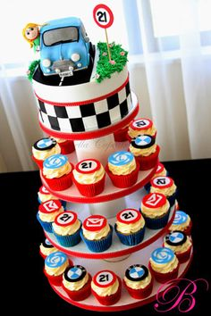 A girl's car-centric 21st birthday cake. Topper is a mini replica of her blue BMW sedan with her popping out the driver's side window. Cupcakes adorned with the BMW logo, the number 21, poker chips, or --- inexplicably --- an envelope mailbox symbol. (Please do let me know if you understand why the last one is there. The source of this cupcake tower is a New Zealand website called Bella's Cupcakes so I was wondering if it was specific to the client or some kind of Kiwi cultural norm that I'm…