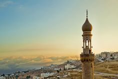 Old mosque minaret overlooking a small town in Jordan, near the capital city Amman